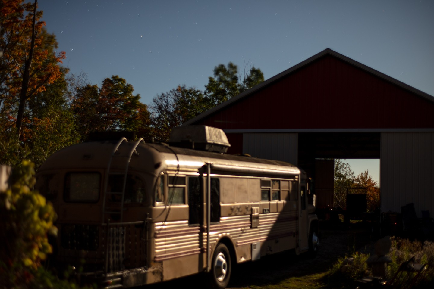 Risher_Wondrous (5 of 7)- This is a landscape orientated digital photograph made outdoors at night. In the photograph from the left sits an old renovated camping bus. The bus is illuminated by the strong moonlight. In front of the bus stands a tall red ba