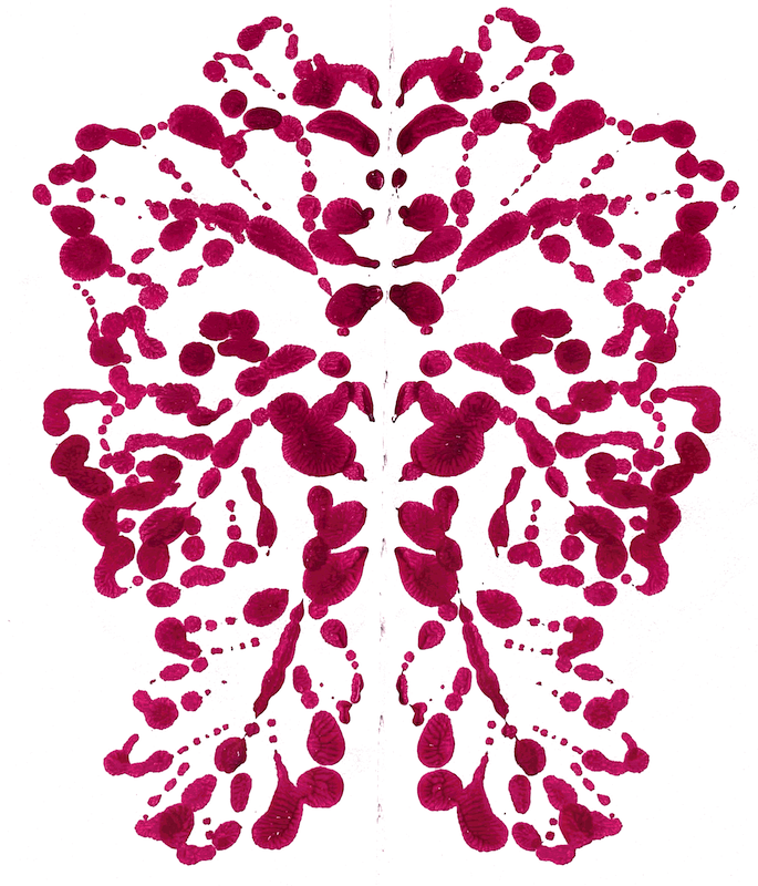 Symmetrical mono print paint in a sketchbook.