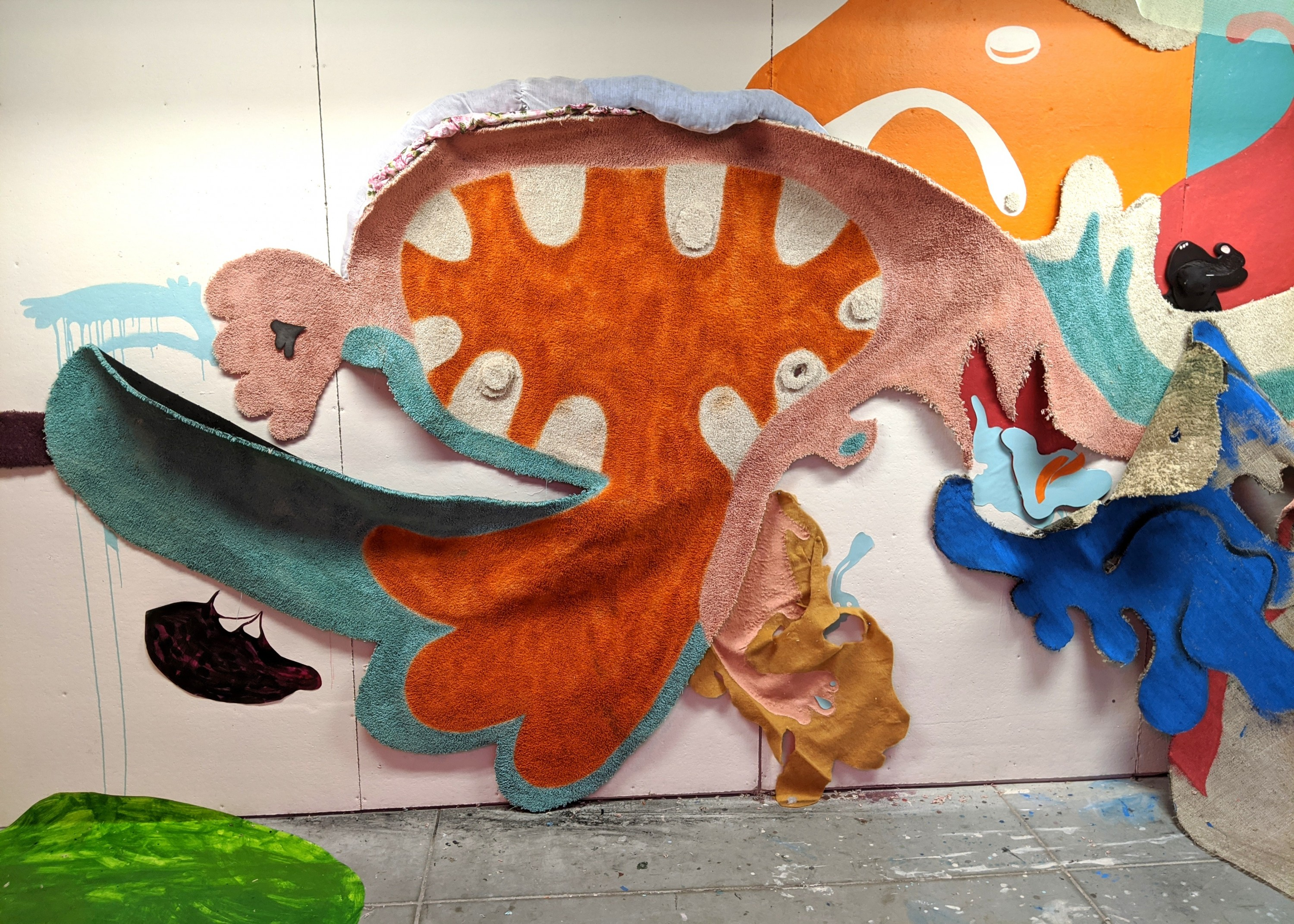 An installation consisting of a large piece of carpet hanging on the wall. The carpet is cut into an abstract, organic shape. It is colored with orange, pink, and blue paint depicting a mouth-like shape in the center. Paint, fabric, and additional smaller