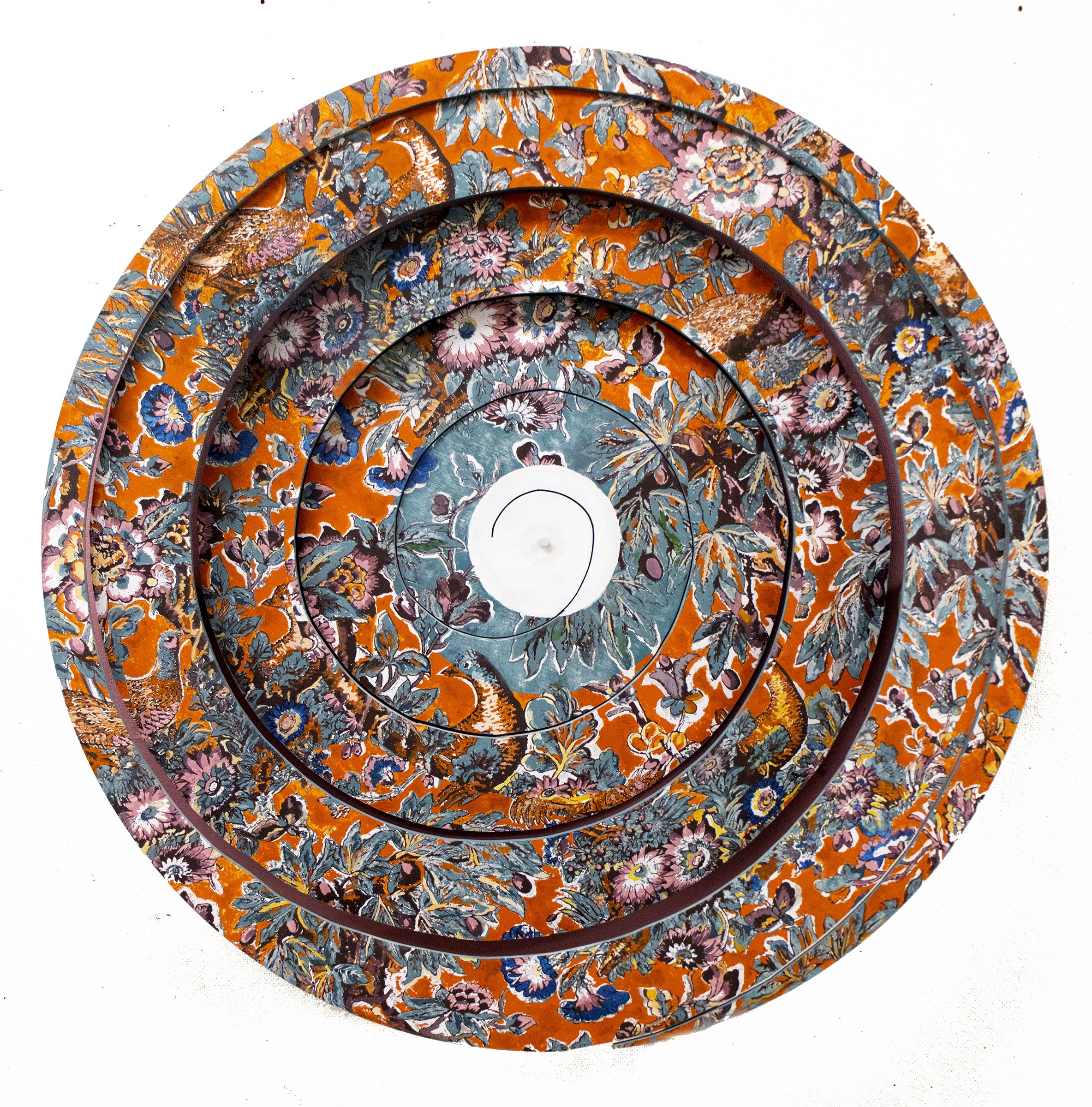 Chintz to Chintzy is a vibrant screenprint on a wooden spiral that stretches outward from the wall. The piece consists of warped motifs of flowers, branches, and birds. The center has a small white circle which then blends into the surrounding pattern.