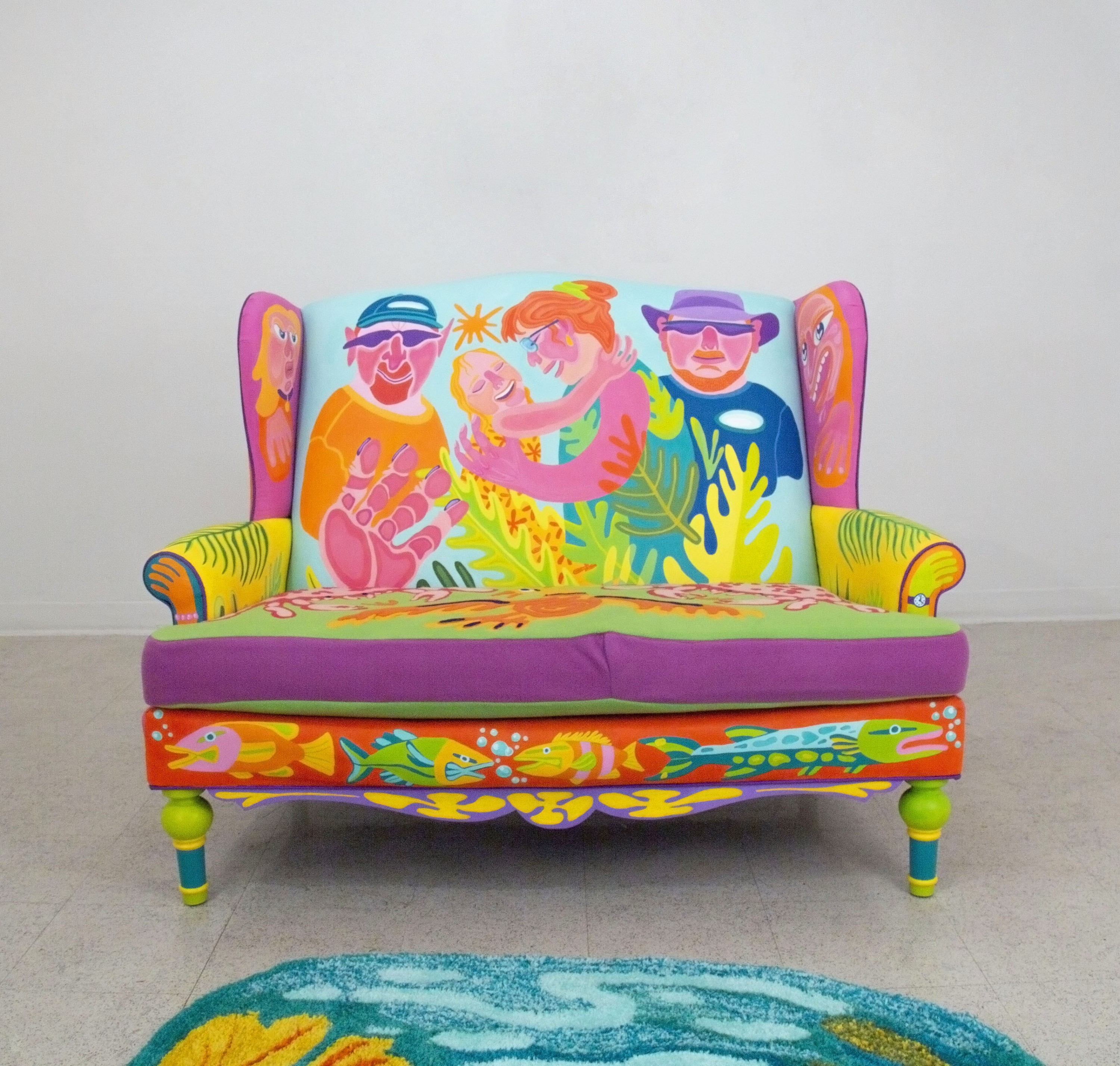 Painted couch with appliquéd cushion cover. Front - Family portrait among palm fronds, fish. Side view - Large flowers, mangrove roots, palmetto leaf. Back -Peacock bass being held among swaying palm trees. Another view shows the couch with two models wea