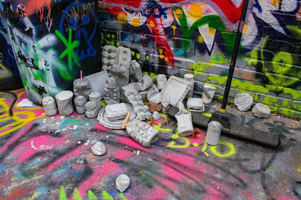 This image shows an arrangement of concrete forms casted from trash produced by the artist, installed in Baltimore's Graffiti Alley.