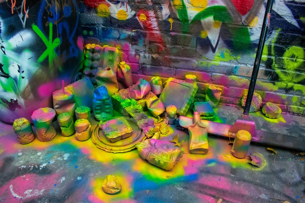 This image shows an arrangement of concrete forms casted from trash produced by the artist and spray painted, installed in Baltimore's Graffiti Alley.