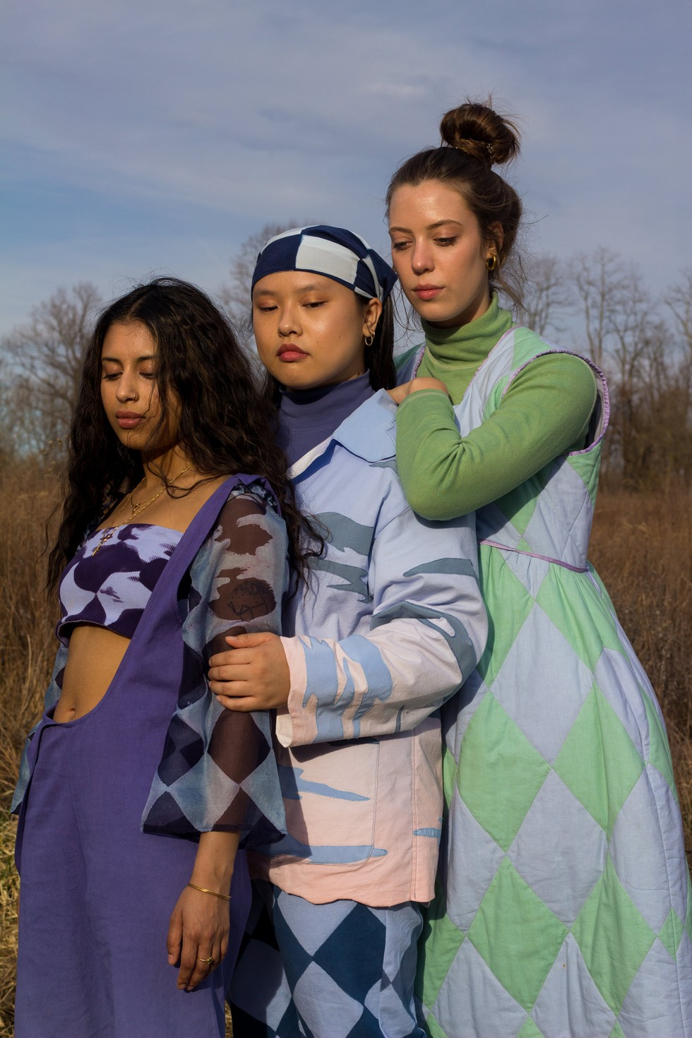 Models standing around lounging in a sunny field wearing flowing, patterned garments