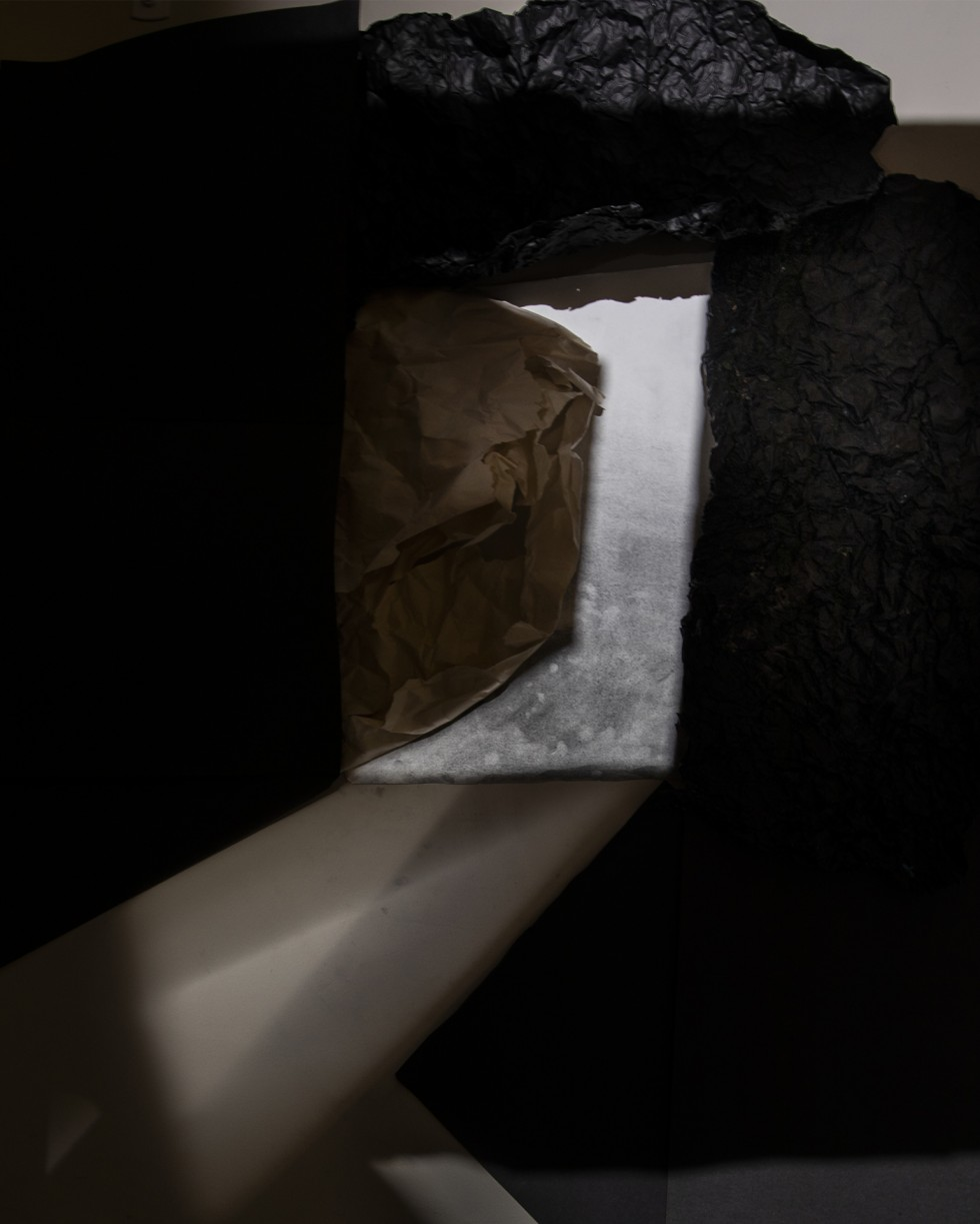 This is a photograph of a collage consisting of paper textures and abstract drawings that trace an outline created by light and shadows. This outline shows a door with light appearing to come out of the door into a darker space.