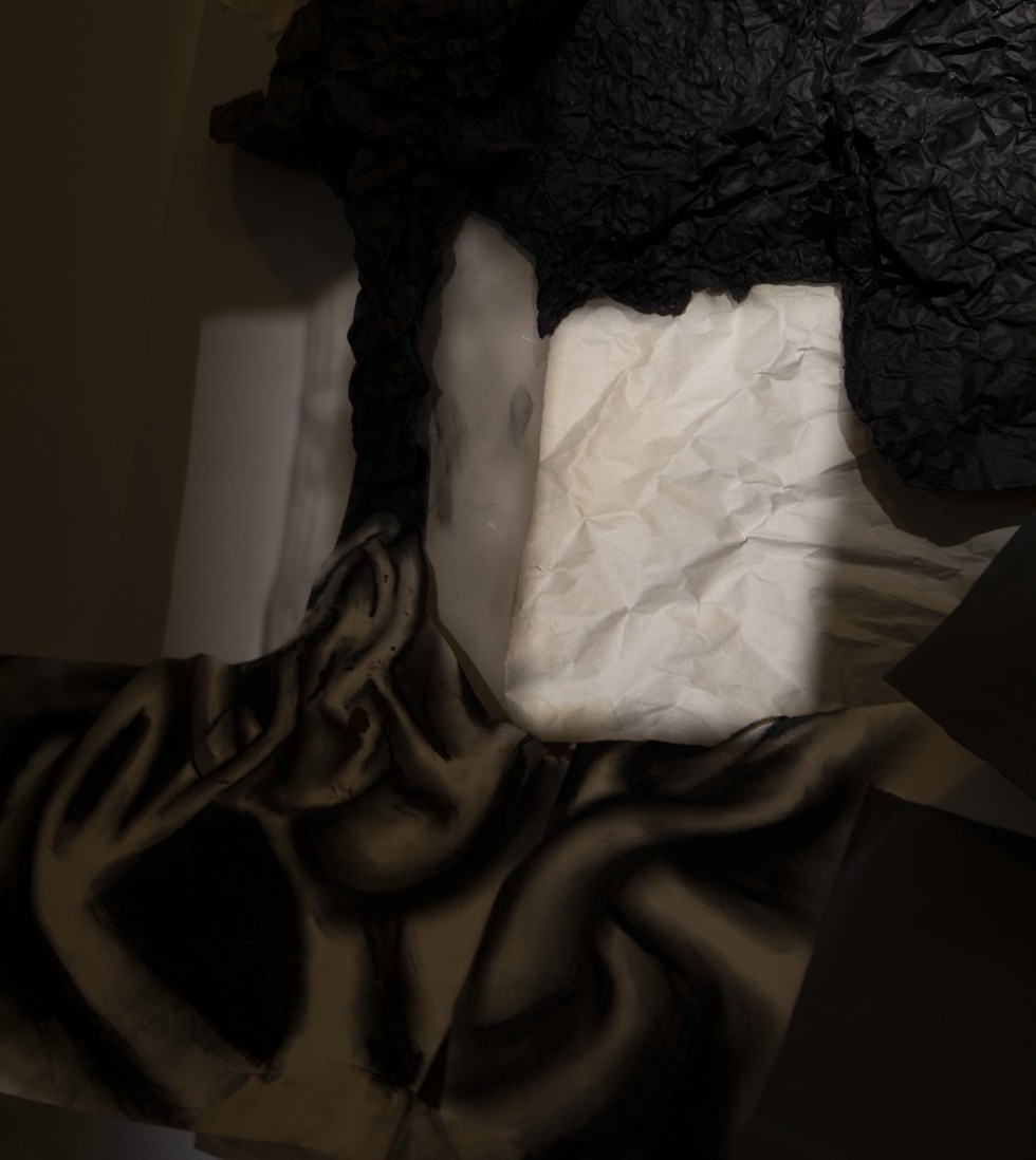 This is a photograph of a collage consisting of paper textures and abstract drawings that trace an outline created by light and shadows. this shadow outline consists of two pockets of light that create two three-demential cubes framing a dark mass that th
