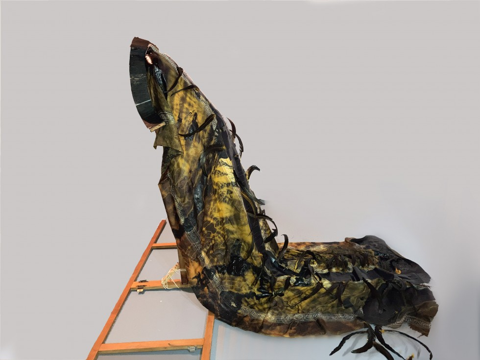 Yellow and black long woven robe decorated with black rooster feathers. The robe is upheld by a wooden armature. On the floor right underneath the robe is a cabinet frame.