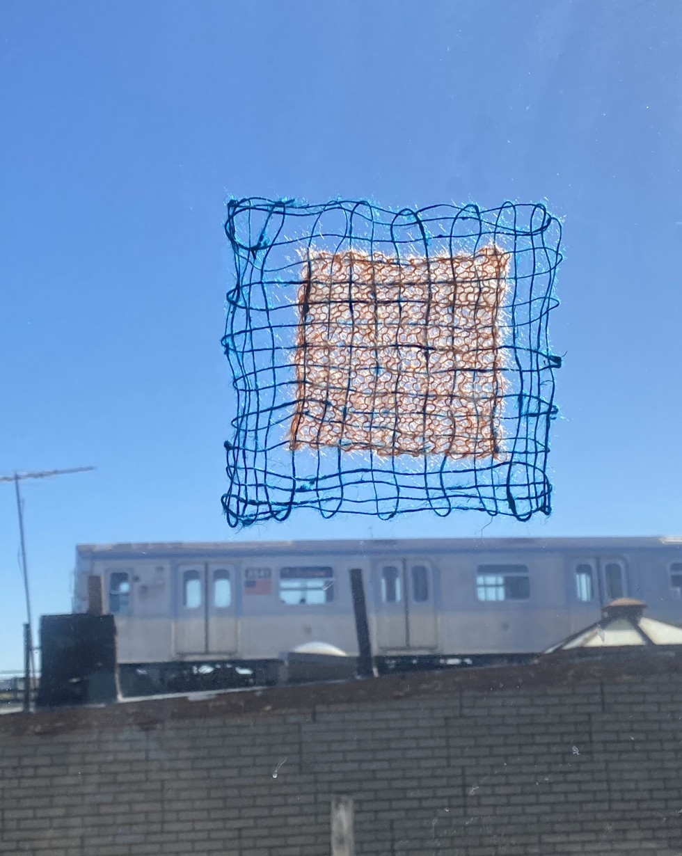 A small weaving affixed to an interior window sits in front of a passing elevated train. The weaving is a lacey blue linen with an orange knit panel at the center.