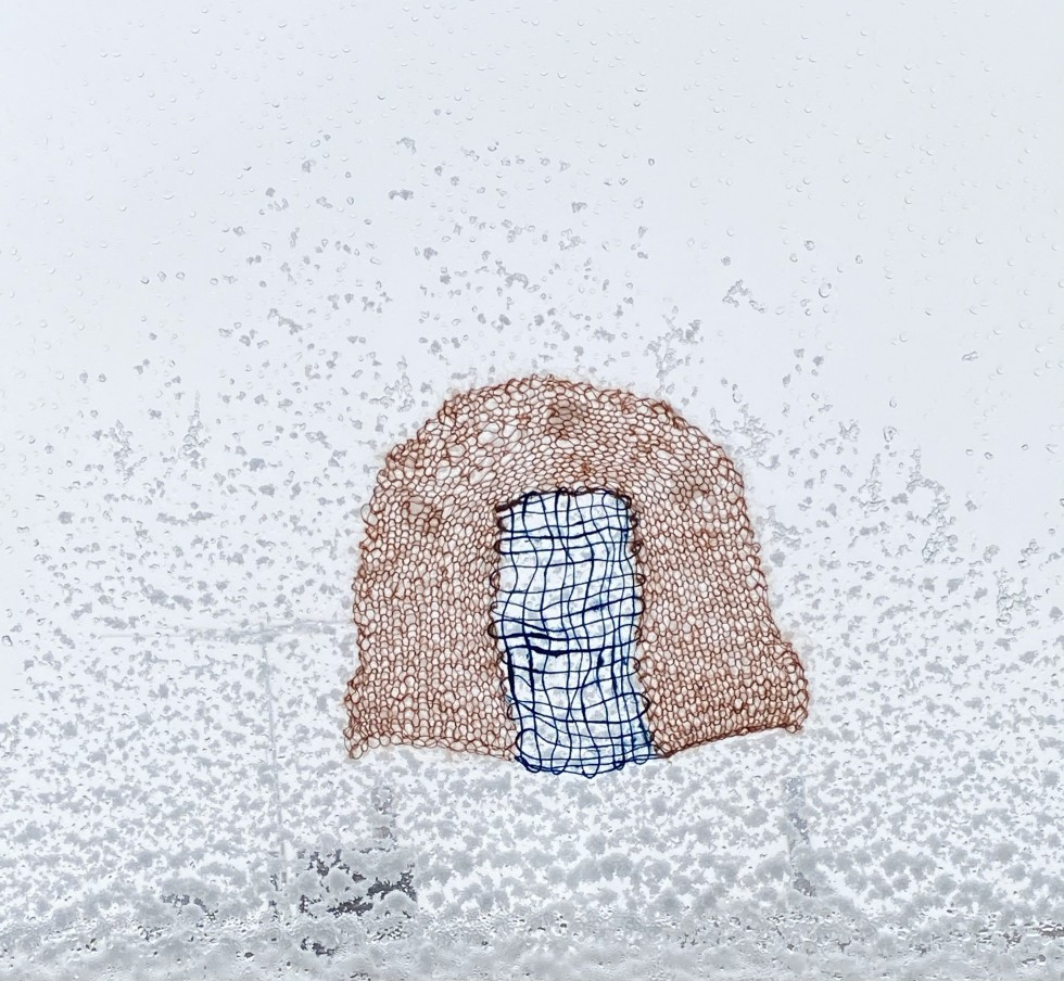a blue weaving is encased in an orange knit arch, the textile is affixed to a window during a morning snowstorm, the snow stuck to the window mimics the shape of the arch.