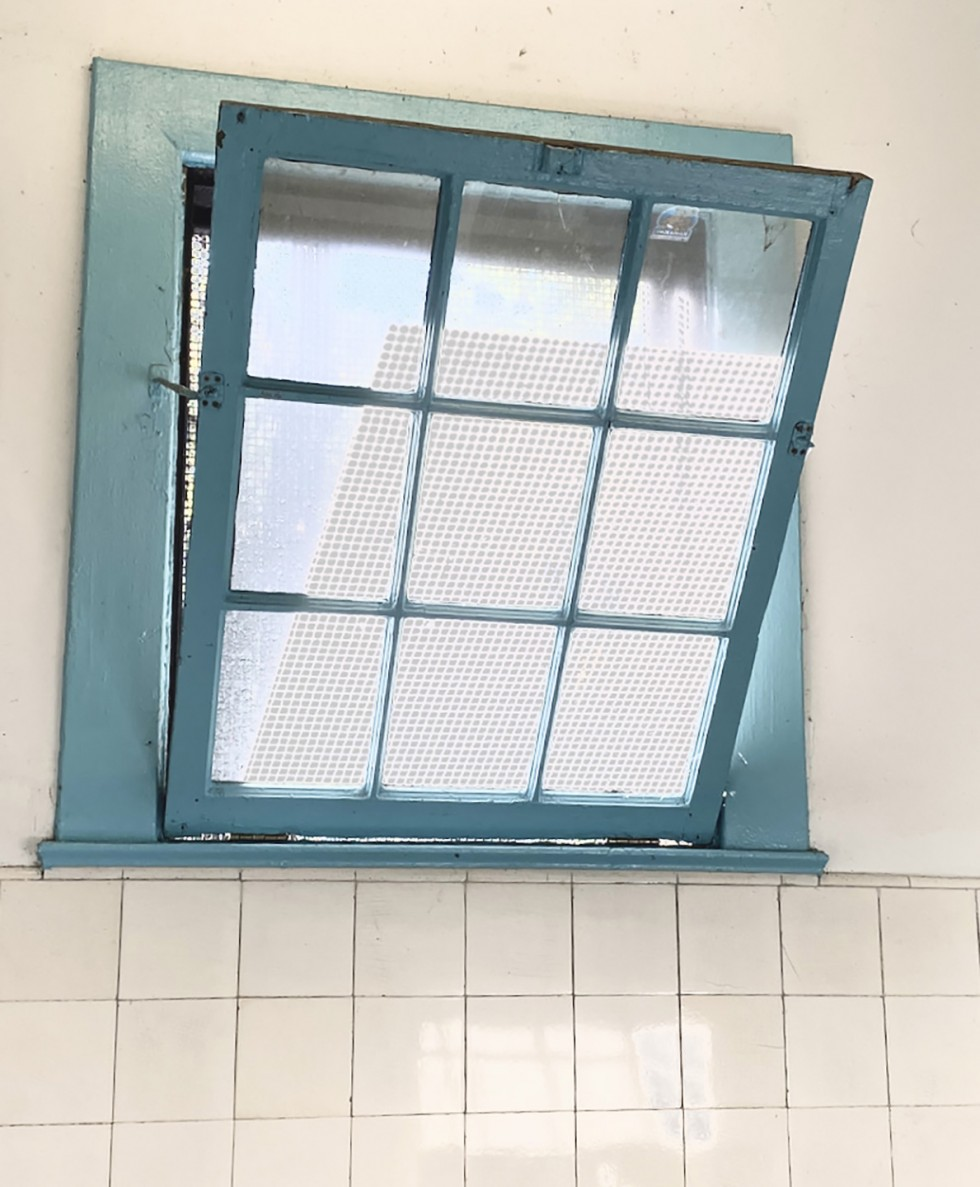 An image of a 9 pane blue window tilted open with white sunlight shining through.
