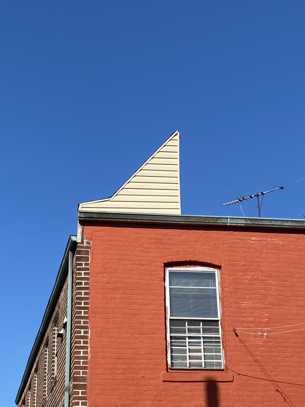 The back of a brick corner row house with a bright red painted wall against a deep blue sky, a triangular roof hatch with cream-colored vinyl siding sits on top of the building. The back window is in the bottom right corner of the image.