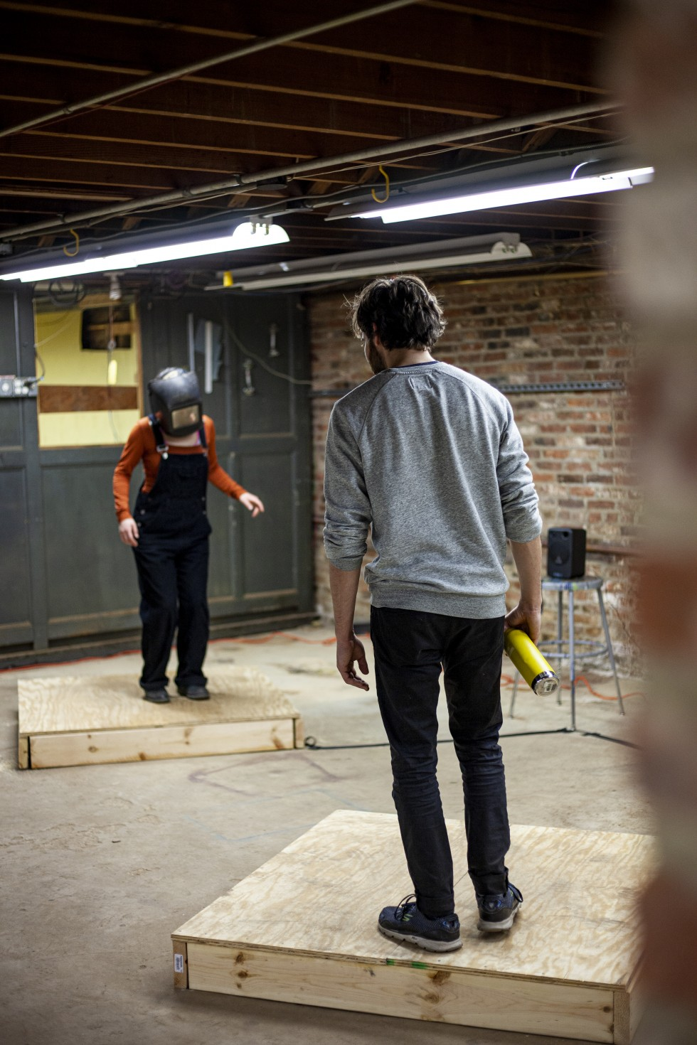 2 people in a room, both standing on a different pallet