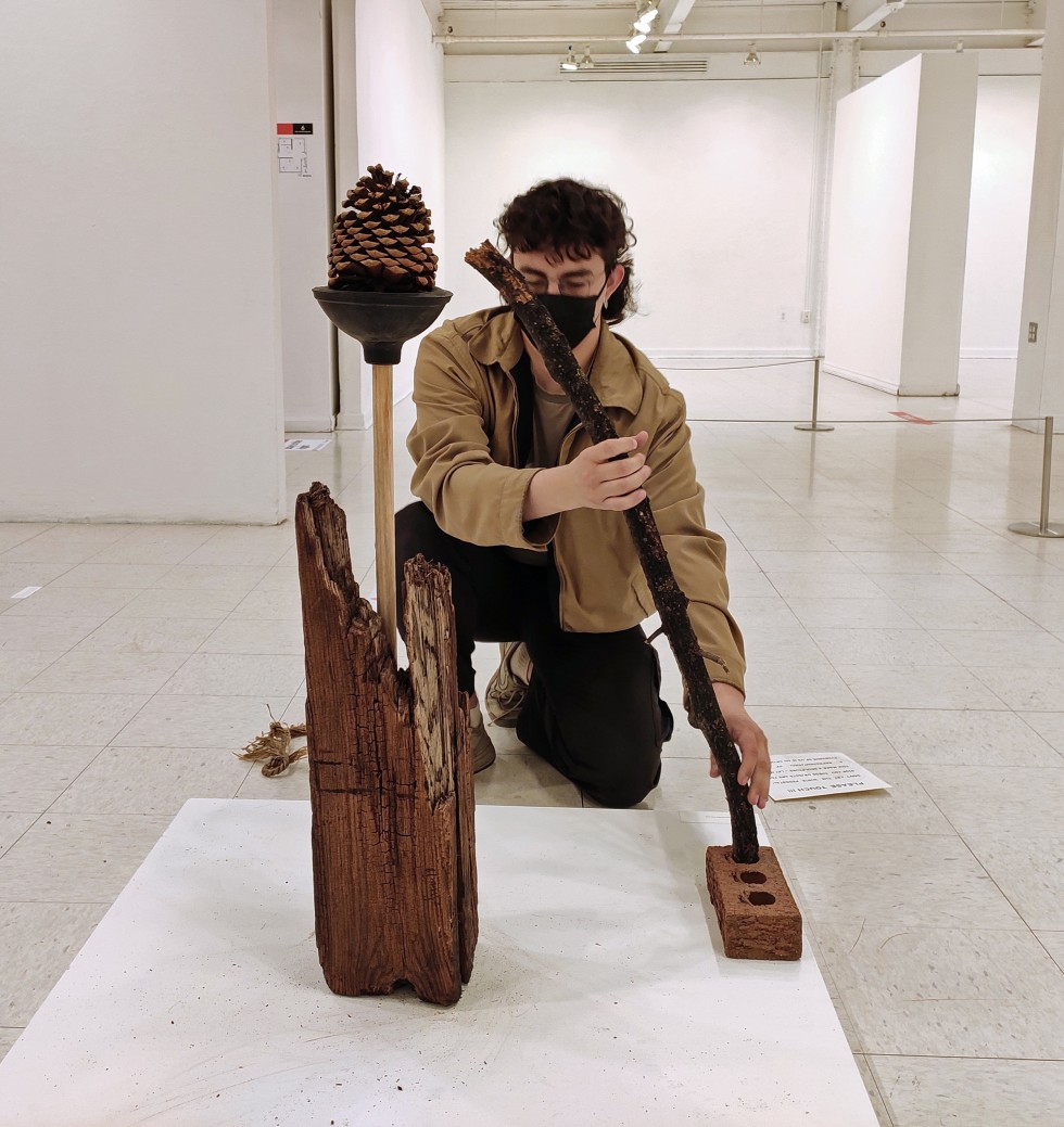 """Interacting participants engaging with an assortment of found objects - wood, plunger, pine cone, brick, tree branch, rope - to make """"self-portraits"""" that best represents them."""