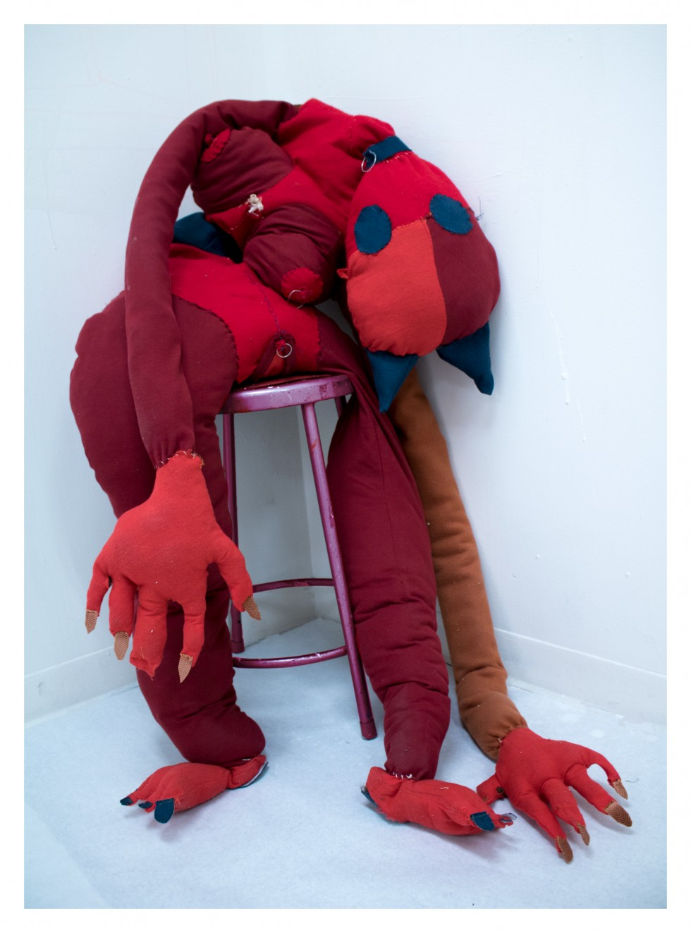 A large soft sculpture of a red, human like cat, is made of felt, and stuffed with wool. The cat is soft sculpture, with pointy ears, and various human like extensions, such as arms, hands, legs, genitals, breasts, fingers and toes. The cat is accessorize