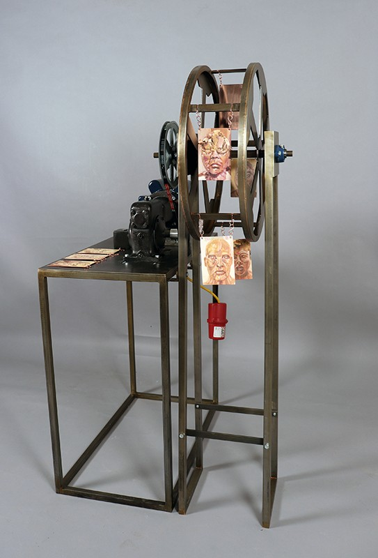 Small scale kinetic Ferris Wheel made from machined steel that turns copper plates with oil painted portraits of people by use of an electronic push button system.