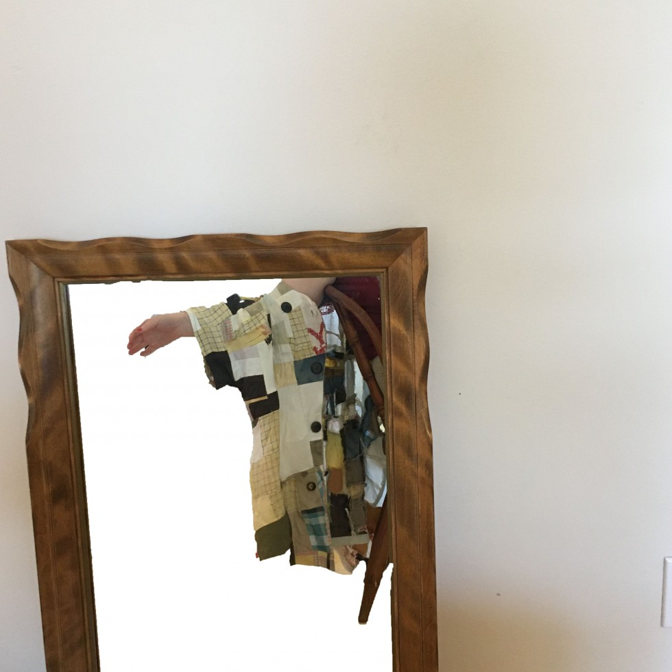 Figure reflected in mirror wearing a patchwork jacket.