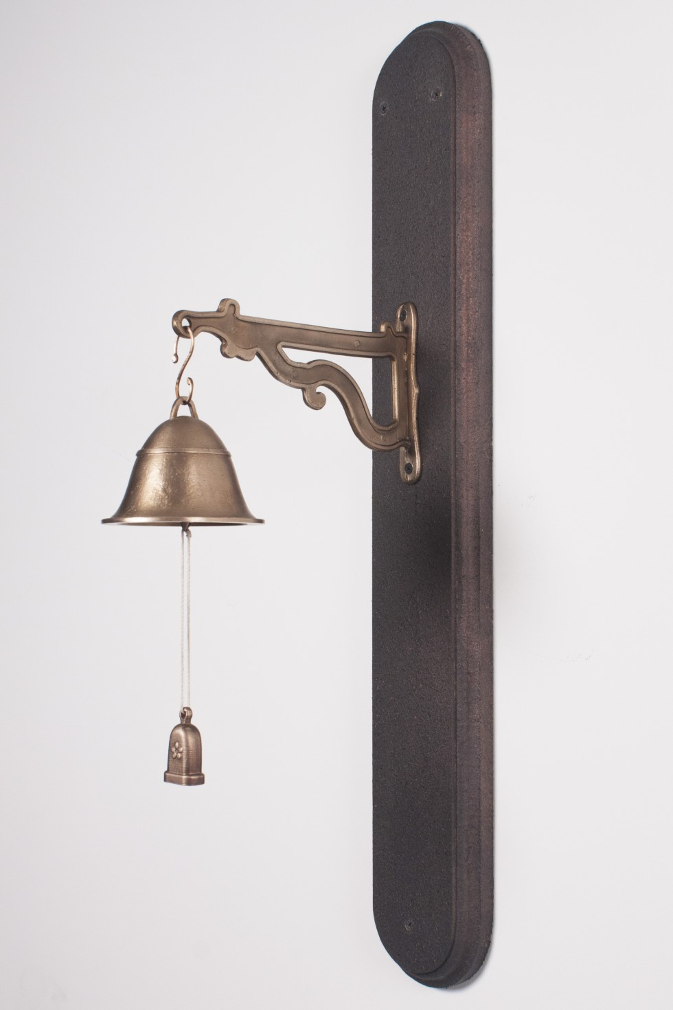Bell (Artifact I) features a cast bronze bell which hangs from a bronze cast mount. The mount is attached to a rough gray oblong plinth on the wall. From the inside of the bell, a small pulley handle hangs from a string, allowing the user of the bell to r