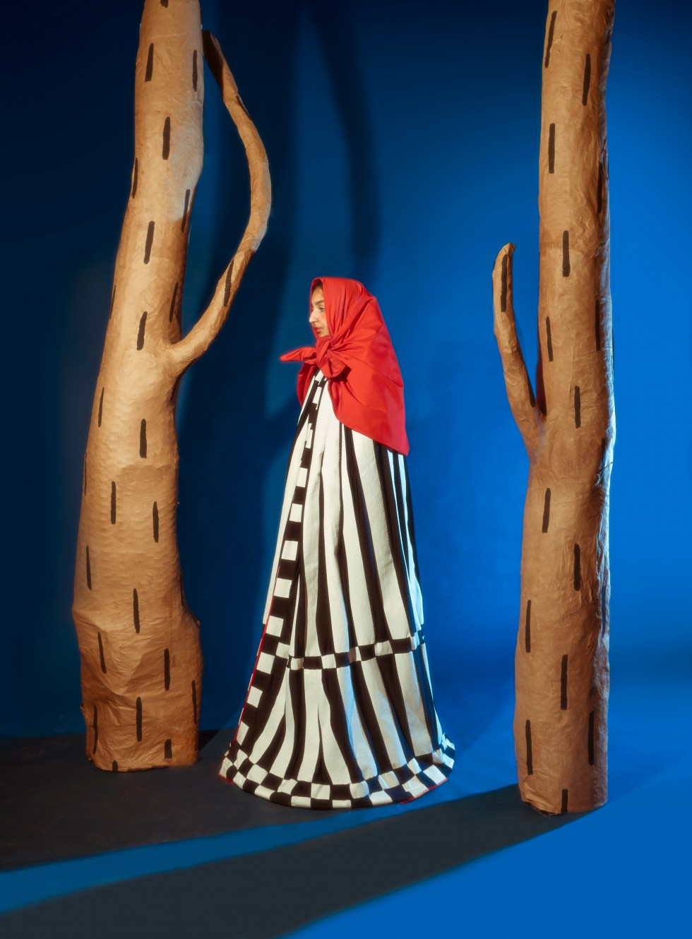 In the first image, the model stands between the two trees in profile facing left. The model wears a black and white piecework cape that is wider at the base, creating a very triangular shape. The model also wears a large red scarf tied around their head.