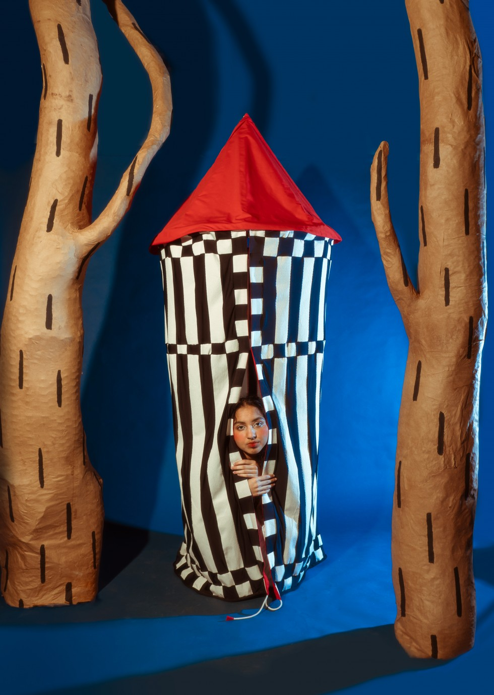 In the second image, the piece now hangs as a ten between the trees. The cape becomes the striped body of the tent and the red scarf is the roof. The model is peeking out of the tent looking directly at the camera, both of their hands resting on the tent