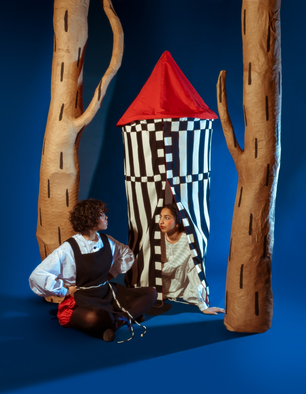 The third image is slightly more zoomed out, now there are two figures. One sits inside the tent wearing a white dress with blue stripes. The model's left arm and face are peeking out of the tent facing the other model. The second model sits in front of t