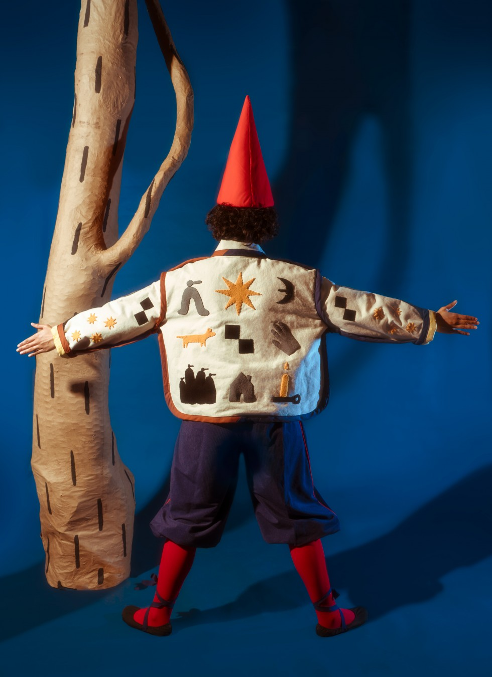 In all the images the piece sits on a blue background with two paper mache trees with a painted black dash pattern. In image one, only one tree is visible on the left side behind the model. The model is facing away from the camera standing with their arms
