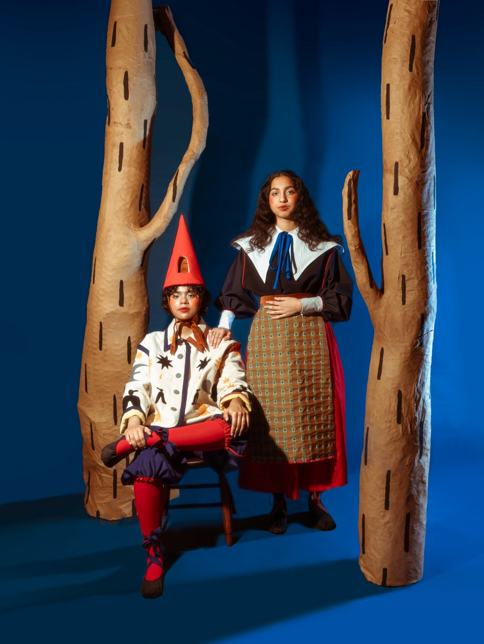 The third image has the same two models in the same outfits. Now they are both facing the camera with the first model sitting in a chair slightly to the left of the middle of the frame. They sit with their left foot resting on their right knee. Their left