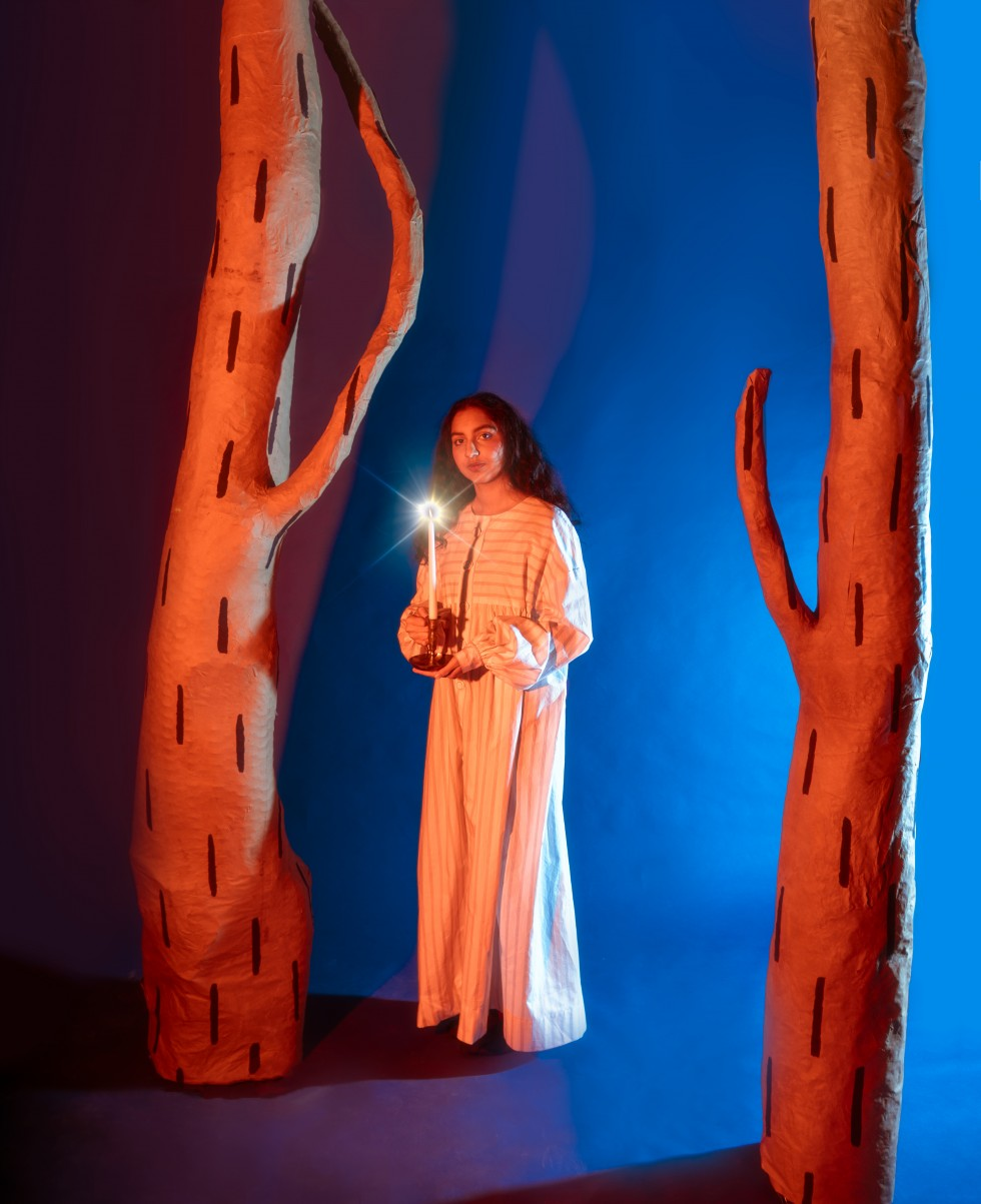 In image one, the model stands in the center of the two trees looking directly at the camera and holding the candlestick in both hands.