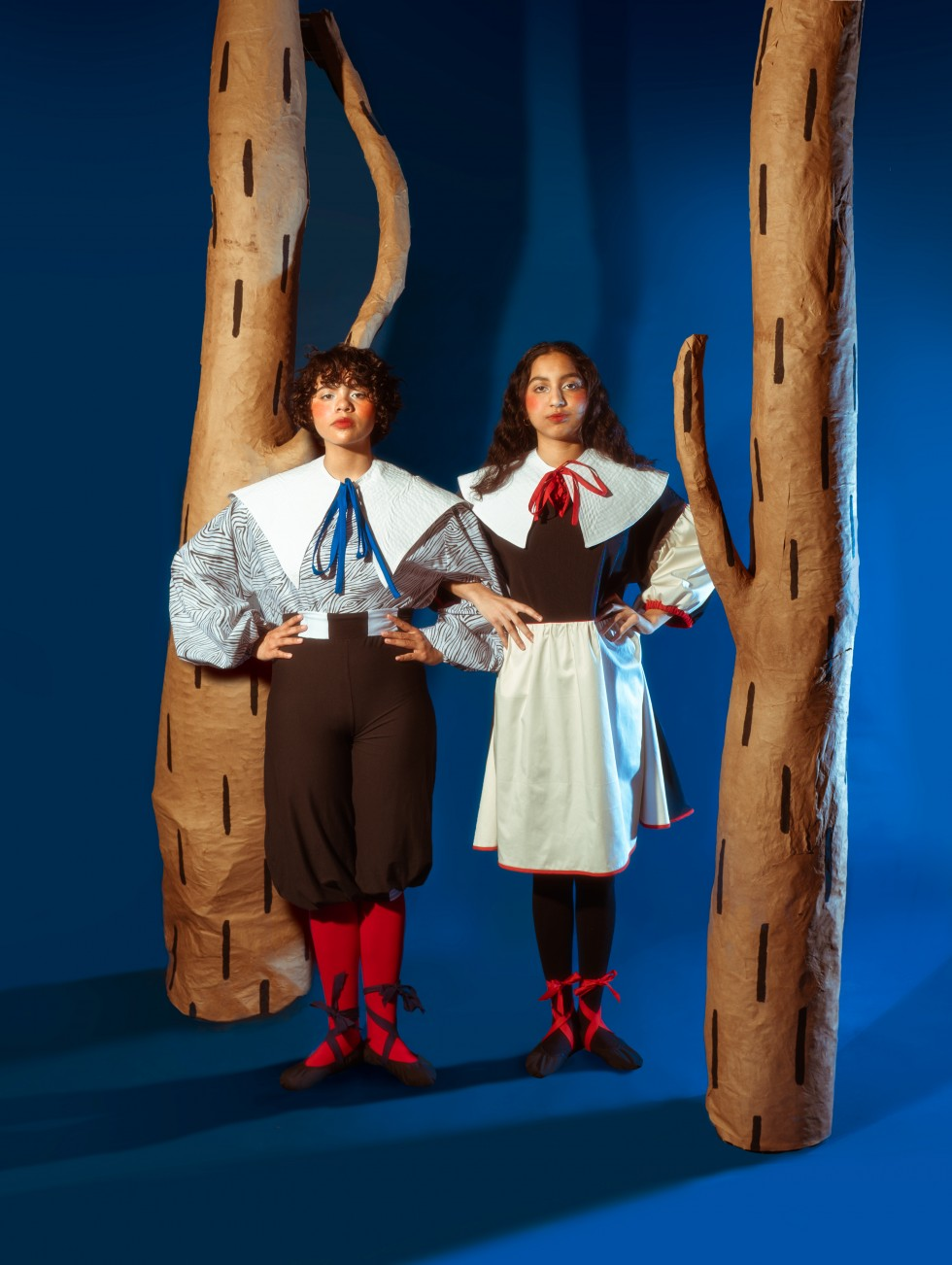 In all the images two figures stand in the middle of the frame in front of a blue background between two paper mache trees that are brown with a painted black dash pattern. In all three images model, one stands on the left side wearing a white shirt with