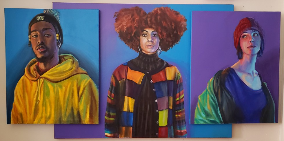 In the middle is a black women with beautiful curly hair and a colorful sweater with a variety of pattern on it. The background is a blend of violet and blue. On the blue side is an overlapping image of a white woman against a violet background, wearing a