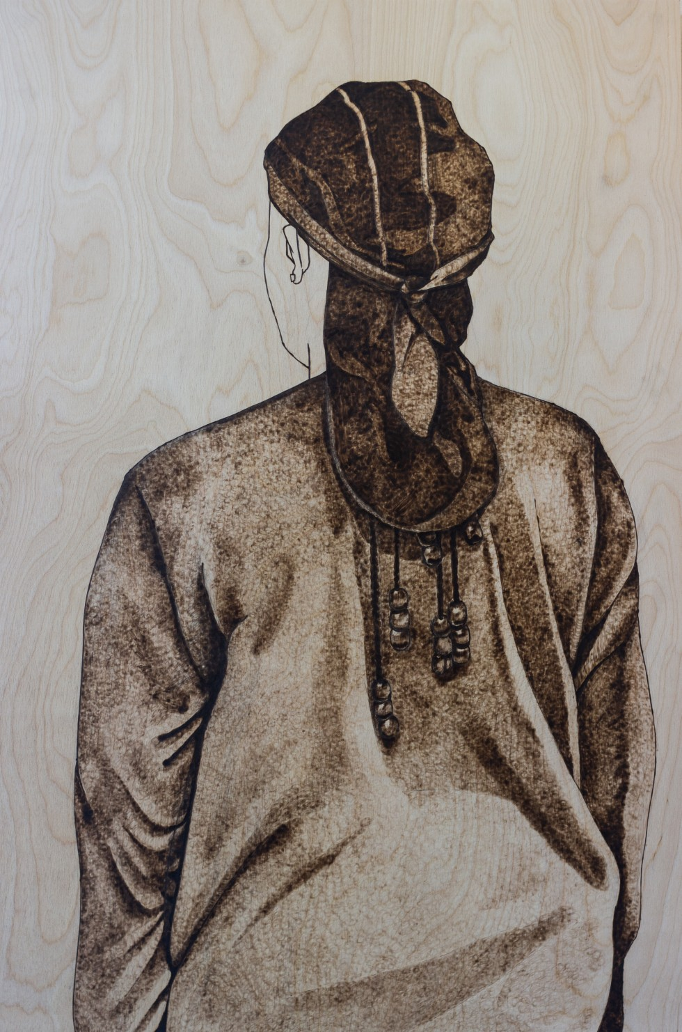 A wood burning of a figure with their back turned wearing a durag.