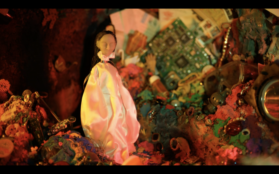 A figure laying in bed jolts awake falling into a cavern of color and clutter. Exploring this cavern, she discovers different objects, then the clutter begins to shift… inching closer…and closer.