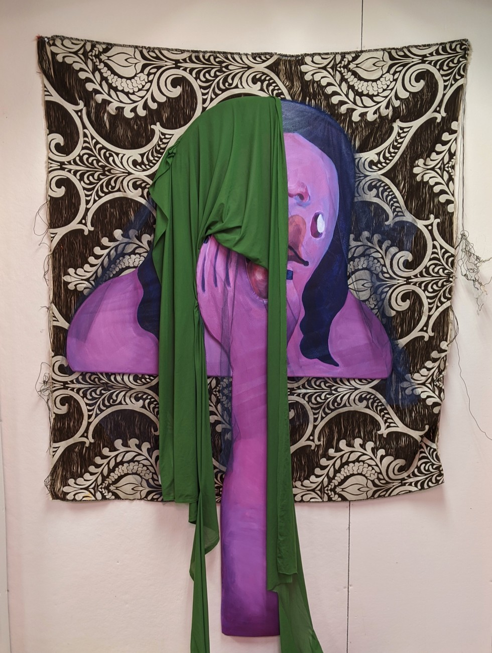 An illustrative, purple arm (made out of shaped and painted plywood) reaches up from the ground, touching a face that is veiled by mesh and green fabric. Underneath this bust is a tan, paisley-patterned tapestry with strings and fibers fraying on the edge