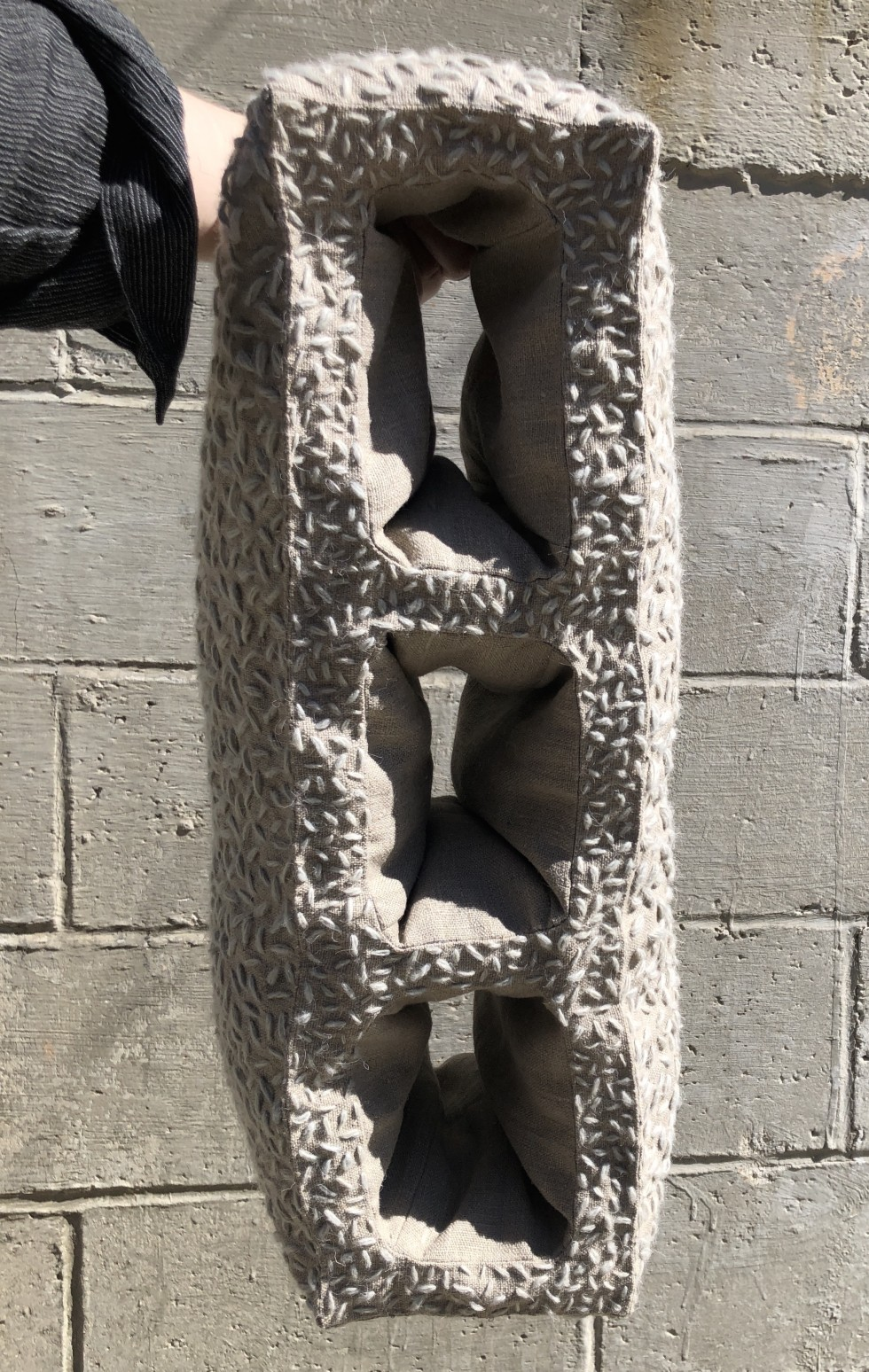 Soft Cinder block is a soft sculpture of a cinder block. It has been edited to be elongated, having three openings instead of one. The block is made of linen and stitched with a thick wool yarn in an irregular pattern to mimic the rough texture of cement.
