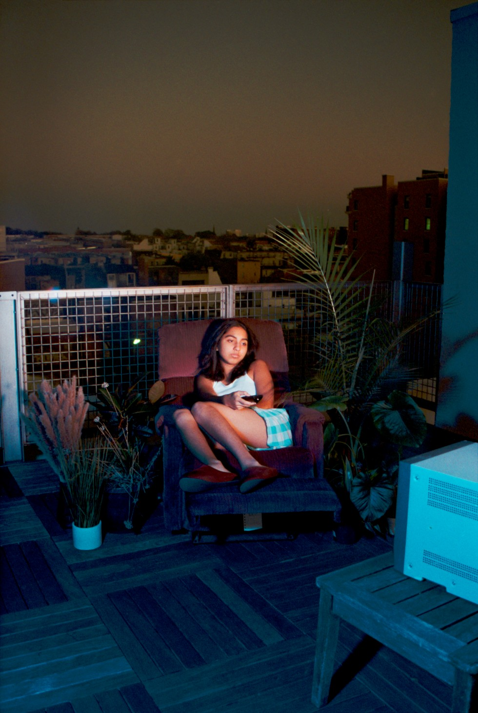 A person sitting in a recliner watching TV on a rooftop