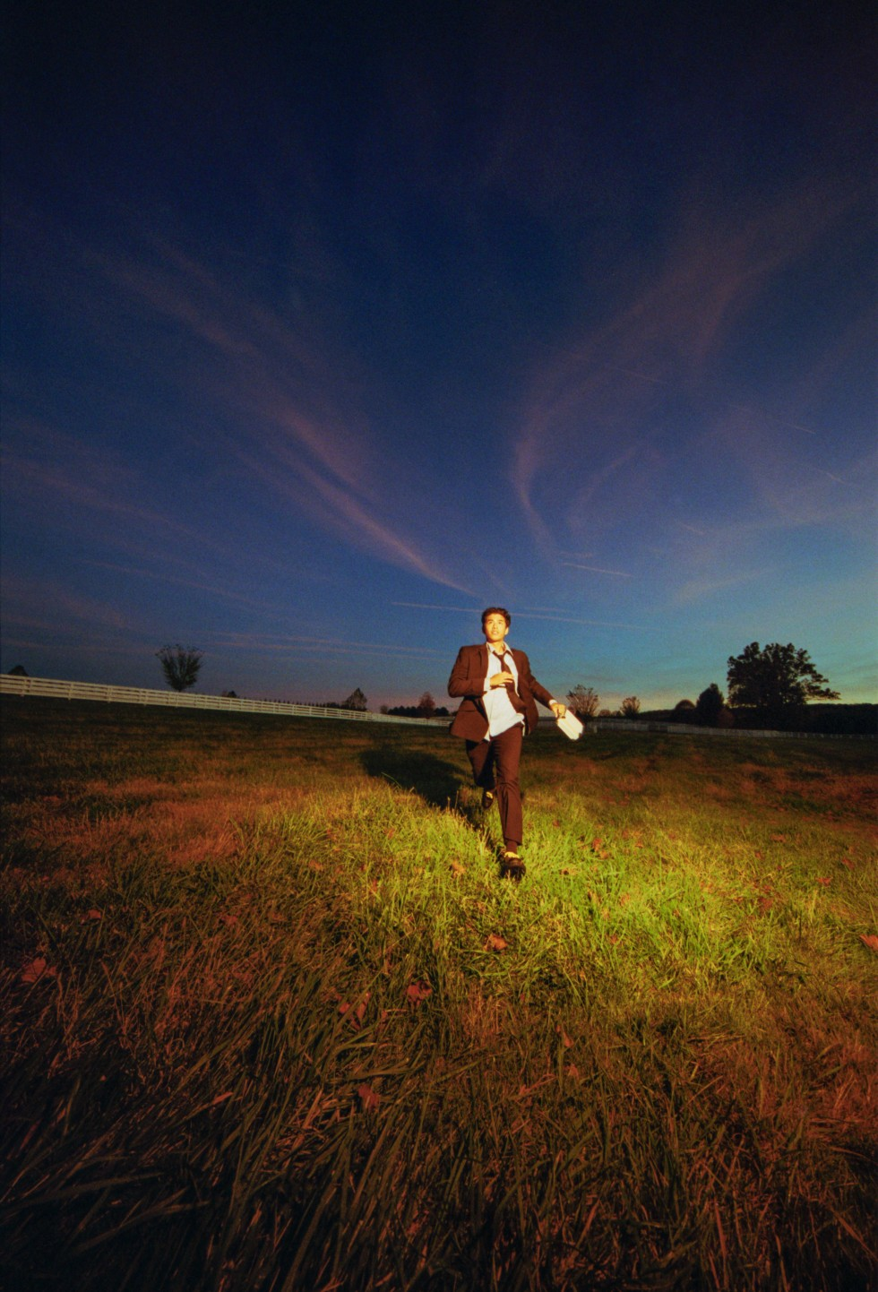 A man running in a field with a light shining on him