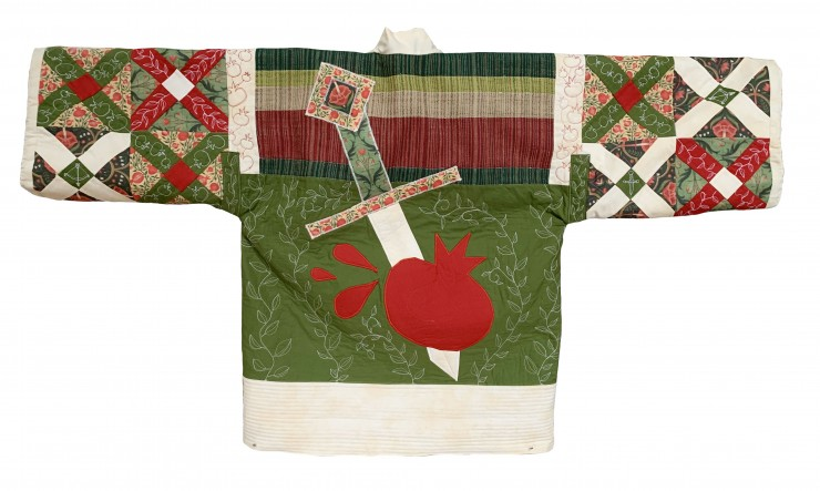 A quilted jacket with freehand machine embroidery forming vines, pomegranates, and swords. The jacket is green, white, and red, with drawstring sleeves and ties in the front. The front has a hand-woven pocket, and the back has an applique of a sword pierc