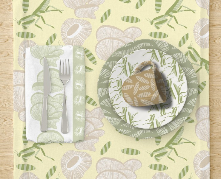 The second image has a cloth napkin under a fork and knife on the left side of the table. The napkin has vertical white and green with large and small mushrooms. To the right there are two plates stacked on top of each other and a mug. The bottom plate ha
