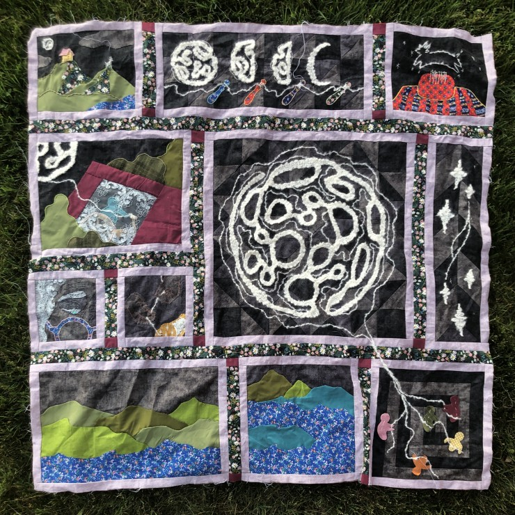 A quilt made up of embroidered squares with imagery about the moon, the sea, and community gathering.