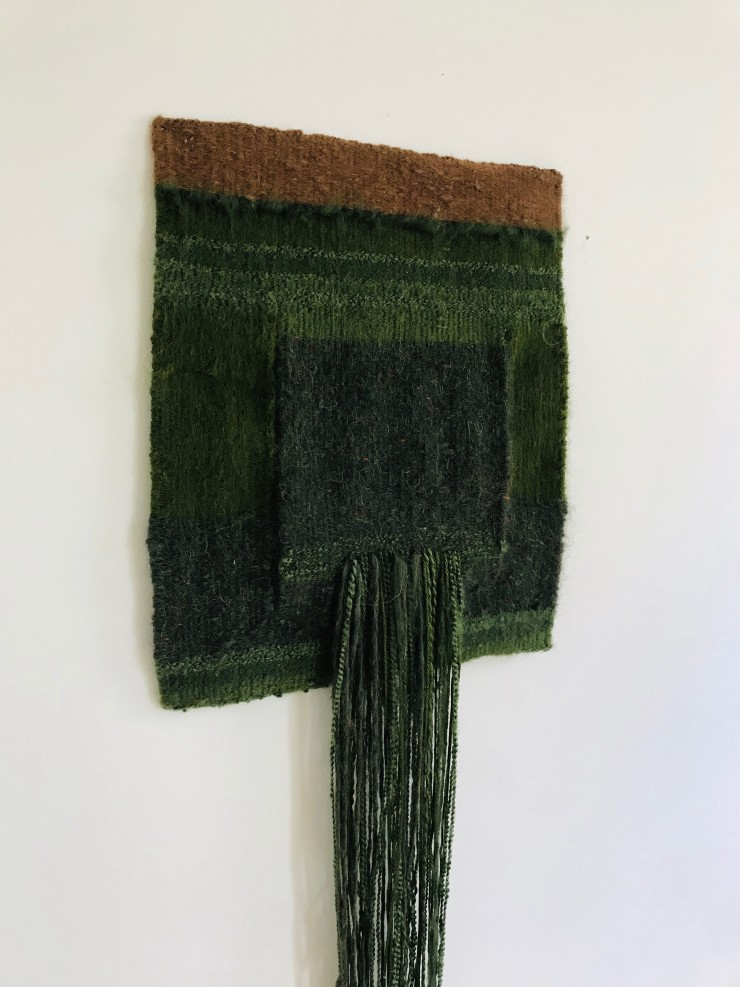Green square with brown block at top and cascading green strings to floor