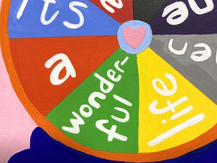 """In the center of this panel is a large circle with an orange band around eight colorful slices. The slices read together, """"it's a wonder-ful life when one has love"""". Every slice has a different word in white. The first is light blue with """"it's"""", the secon"""