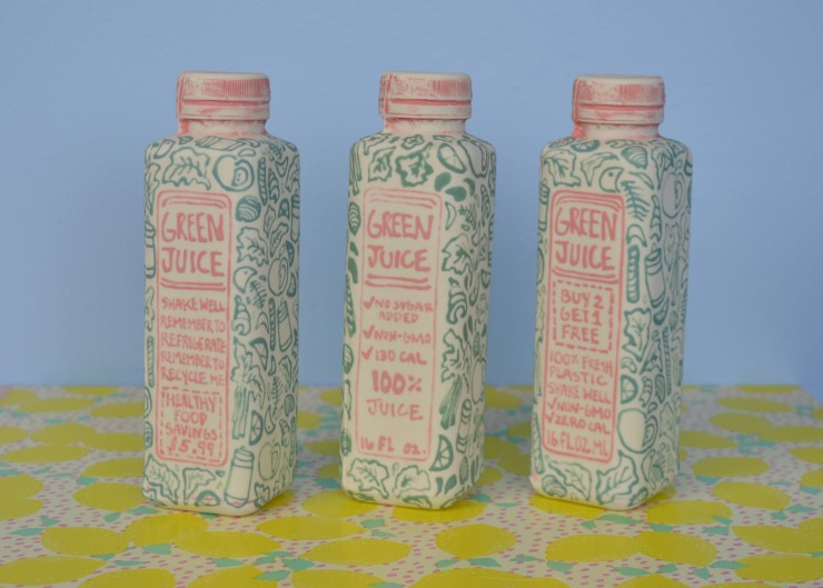 Close up view of 3 slip-casted ceramic bottles. The ceramic bottles are in the shape of plastic rectangular bottles. The bottles are facing forward, positioned at a three-quarter view point. On the front of the bottle is a label identifying the bottles as