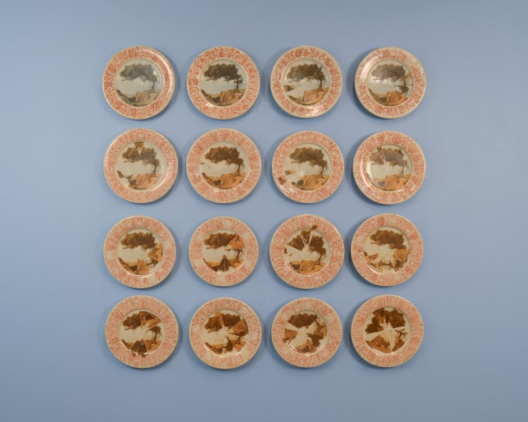 Full view of 16 ceramic plates hanging on a sky-blue wall. The 16 plates are arranged in a 4 x 4 square. The full set of plates spans about 36 in x 36 in on the wall. Each plate is about 8 inches in diameter. The center of each plate is decorated with an