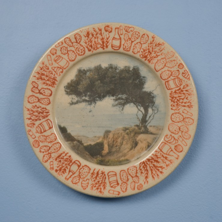 Close up shot of a single ceramic plate. The plate is about 8 inches in diameter, hanging on a sky-blue wall. It is the first plate in the set of 16 plates. The center of the plate is decorated with an image of a tree on a cliffside that overlooks the oce