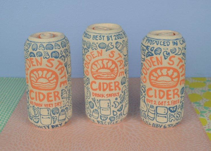 Close up view of 3 ceramic, handbuilt cans. The cans are facing forward, showing the label identifying them as 'Golden State Cider'. Under the label, each can has a different subtitle. For the subtitles, the can on the left states 'No Rain Very Dry', the