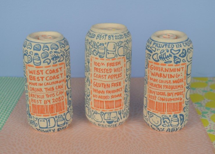 Close up view of 3 ceramic, handbuilt cans. The cans are facing backwards, showing the label on the backside of the cans. The label is rectangular, containing different text and ingredients on each can. The text is written in orange underglaze. A pattern
