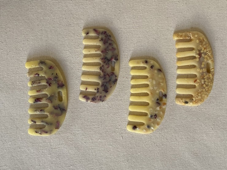 A collections of four comb molds made out of beeswax and encasing dried rose petals, corn kernels and guajillo chili pepper seeds.