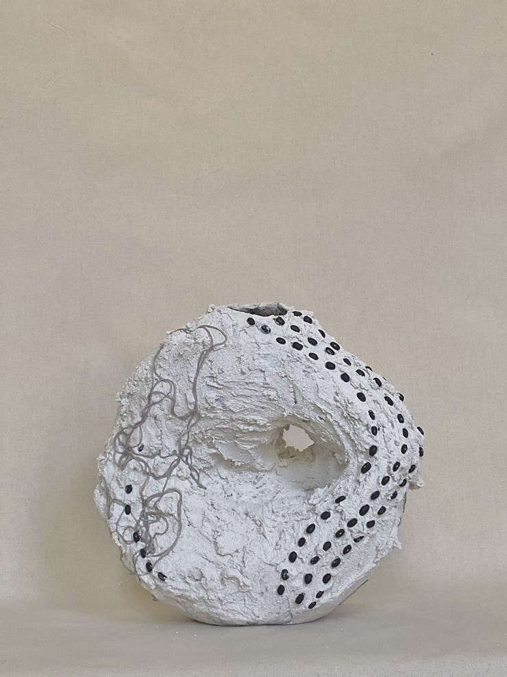 A White Vessel made out of grout and paper mache' in the shape of a circular mountain .With a hole off centered decorated with black beans and black bean dyed yarn.