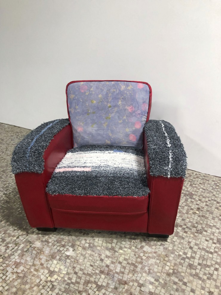 Photograph of a red leather sofa chair in front of a white wall with tile floor. The seat and arms of the chair are covered with black and white carpet with pink and blue accents, the back of the chair is covered with purple canvas with pink and green flo