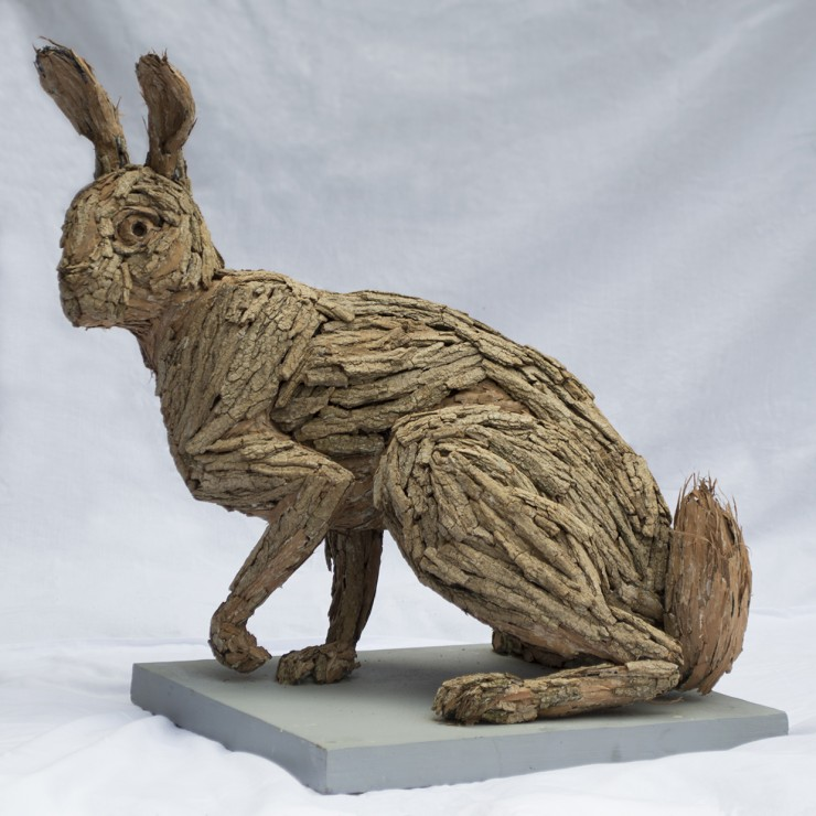 A sculpted Hare jumping away from the viewer created out of Black Locust Bark.