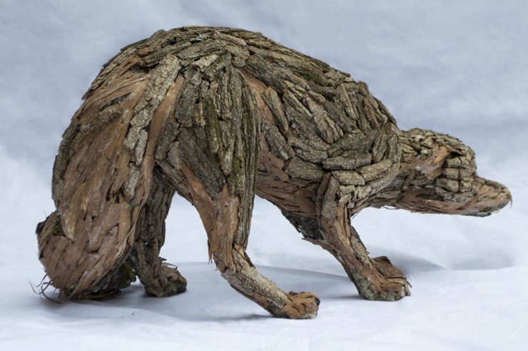 A sculpted fox that is cowering backwards. The surface is created with bark from a Black Locust Tree, each muscle is defined from how the bark is methodically placed.